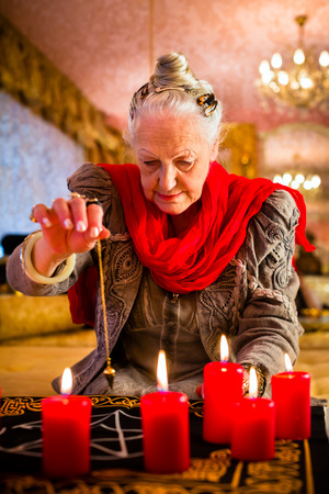 interpret: Female Fortuneteller or esoteric Oracle, sees in the future by dowsing her pendulum during a Seance to interpret them and to answer questions