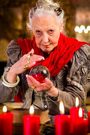 adivino: Fortuneteller Mujer o esotérica Oracle, ve en el futuro mirando en su bola de cristal Foto de archivo