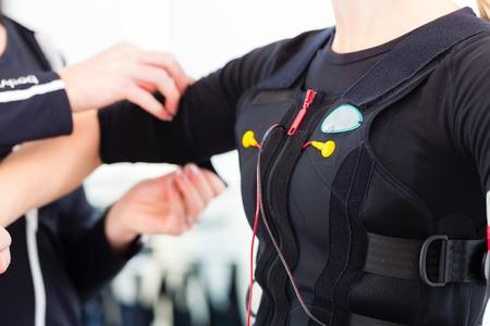 fisioterapia: Mujer mujer vestido de entrenador en ems electro estimulaci�n muscular de traje