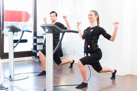 Allenatore femminile che dà l'uomo e la donna lo SME elettro esercizio stimolazione muscolare