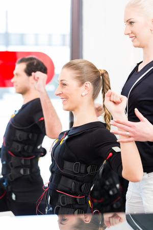 electro: Weibliche Trainer geben Mann und Frau ems elektro Muskelstimulation �bung Lizenzfreie Bilder