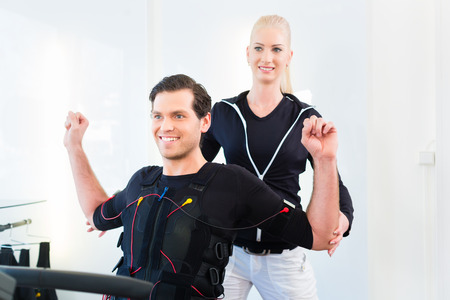 stimulation: Female personal trainer giving man ems electro muscular stimulation exercise