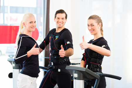 stimulation: Female coach giving man and woman ems electro muscular stimulation exercise