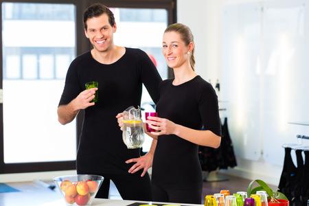 man drinking water: Man and woman having break in fitness studio drinking water