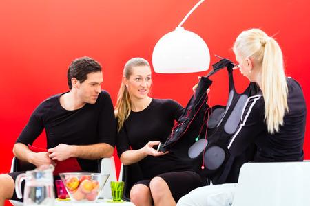 Female coach explaining couple ems electro muscular stimulation costume