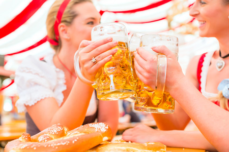 folk festival: Friends drinking together Bavarian beer in national costume or Dirndl on Oktoberfest