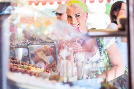 candy apple: Woman eating candy apple at Oktoberfest wearing Dirndl