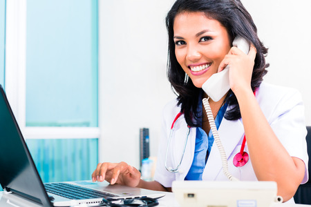 telephoning: Asian female doctor working and telephoning in office or medical practice