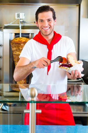 pinchos morunos: Doner Kebab - vendedor agradable en un restaurante de comida rápida turca, con un pan de pita recién hecho o kebab Foto de archivo