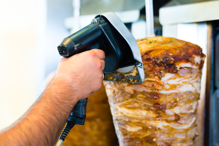 turk: cutting meat with sharp electrical knife in front of skewer