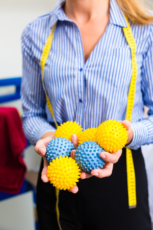drycleaning: Female cleaner in laundry shop or textile dry-cleaning with drying or washing balls