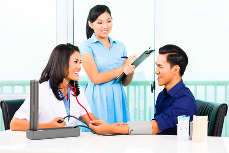 Asian female doctor check-up blood pressure on patient while nurse writing on clipboard Stock Photo