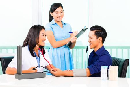 Aziatische vrouwelijke arts check-up van de bloeddruk van de patiënt terwijl de verpleegkundige die op klembord Stockfoto