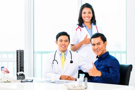 grupo de mdicos: Doctor asi�tico dando apret�n de manos del paciente para la curaci�n completa en la pr�ctica o la cirug�a