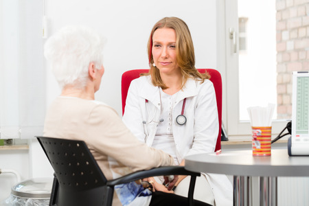 geriatric: Young female doctor sitting with pensioner in surgery consultation hour at desk