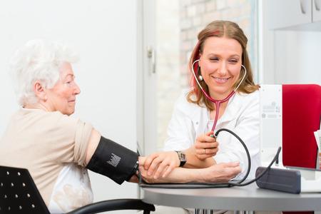 若い女性医者測定血圧先輩患者の外科診療時間 写真素材
