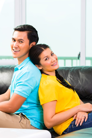 longterm: Young Asian handsome couple having long-term relationship sitting on sofa or couch