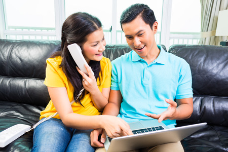 Young Asian handsome couple calling the costumer hotline for online booking, using laptop and phone on couch