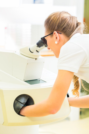 Female dental technician or orthodontist  controlling denture with microscope and grinder photo