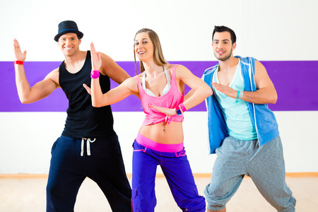 Group of men and women dancing fitness choreography in dance school photo