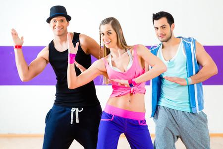coreografia: Grupo de hombres y mujeres que bailan coreograf�a de fitness en la escuela de baile
