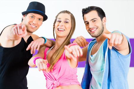 baile hip hop: Grupo de hombres y mujeres que bailan coreografía de fitness en la escuela de baile