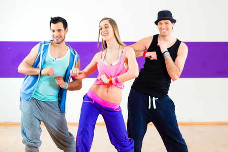 choreography: Group of men and women dancing zumba fitness choreography in dance school