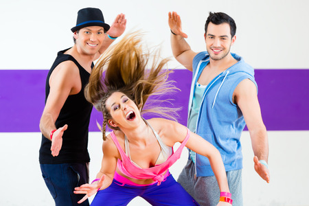 hip hop pose: Group of men and women dancing zumba fitness choreography in dance school