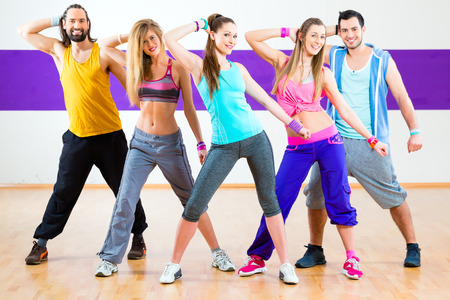 dancing pose: Group of men and women dancing fitness choreography in dance school