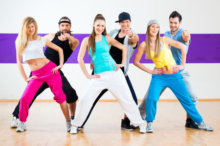 zumba: Young men and women dancing modern group choreography in dance school