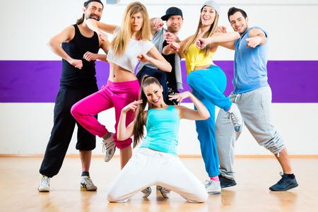 Jonge mannen en vrouwen dansen moderne groepschoreografie in dansschool