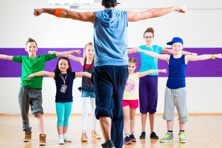 Dance teacher giving children fitness class in gym Imagens