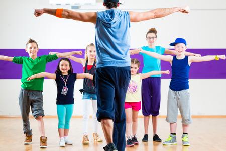 Dance teacher giving children fitness class in gym Foto de archivo