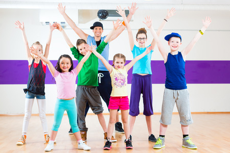 kids class: Dance teacher giving children fitness class in gym Stock Photo