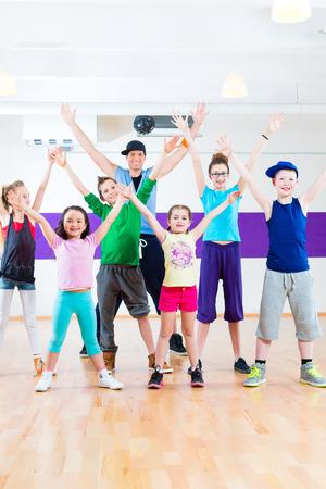 dance teacher: Dance teacher giving children fitness class in gym Stock Photo