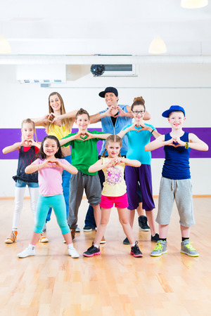 Dance teacher giving children fitness class in gym Stock Photo