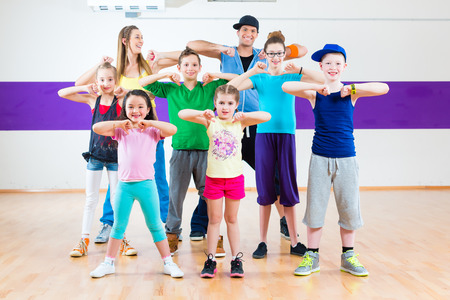 dancing pose: Dance teacher giving children fitness class in gym Stock Photo