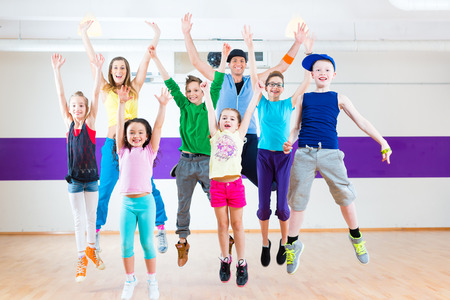 Dance teacher giving children fitness class in gym Stockfoto