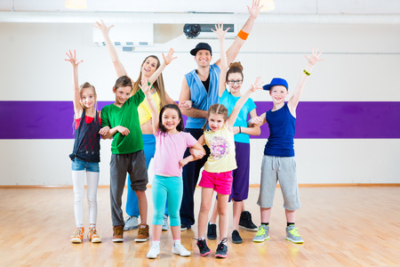 kids class: Dance teacher giving children  fitness class in gym