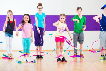 Children dancing modern group choreography with scarfs Foto de archivo