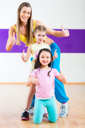 Young dancing teacher training children in modern group choreography photo