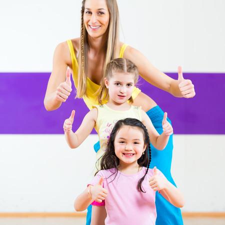 hip hop girl: Young dancing teacher training children in modern group choreography