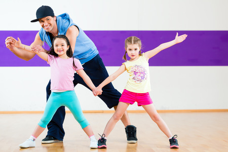 Young dancing teacher training children in modern group choreography