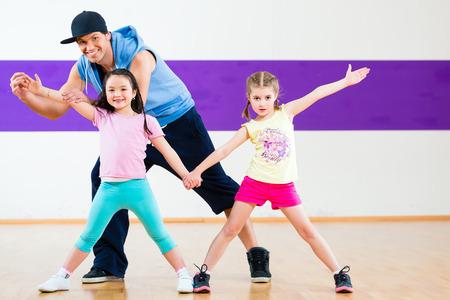 teacher training: Young dancing teacher training children in modern group choreography