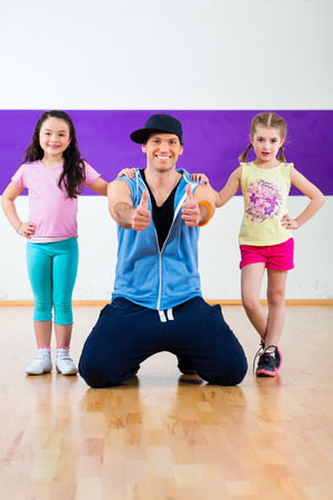 Young dancing teacher trainin children in modern zumba group choreography photo