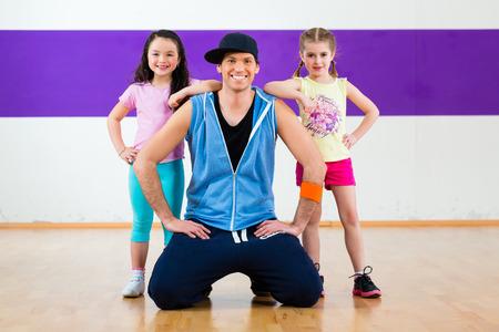 tanzen: Junge Tanzlehrer trainin Kinder in der modernen Zumba Gruppenchoreographie