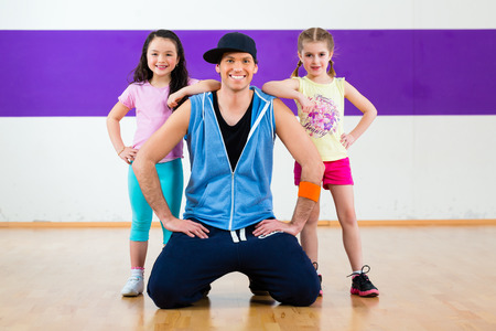 dancing pose: Young dancing teacher trainin children in modern zumba group choreography Stock Photo