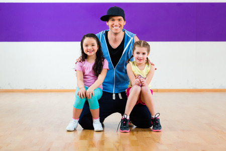 Young dancing teacher trainin children in modern group choreography photo