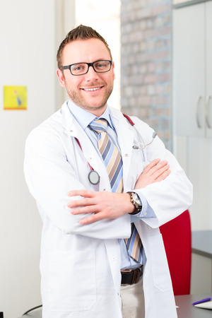 male doctor: Young doctor in surgery at desk