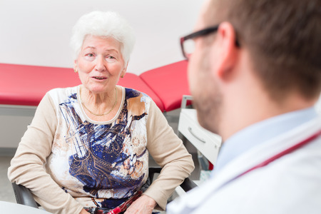 medicate: Doctor sitting with pensioner in surgery consultation hour at desk